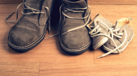 Closeup of father's shoes close to child's shoes on a parquet