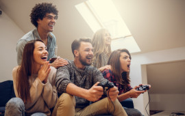 Group of excited friends playing video games at home.